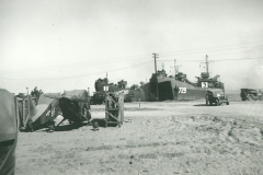 104_Luzon_Preparing_to_ship_out_to_Korea_note_disassembled_aircraft_on_the_beach