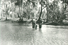 50_Milne_Bay_Tom_Fallen_and_Ezra_McCray_carry_a_5_gallon_can_of_water