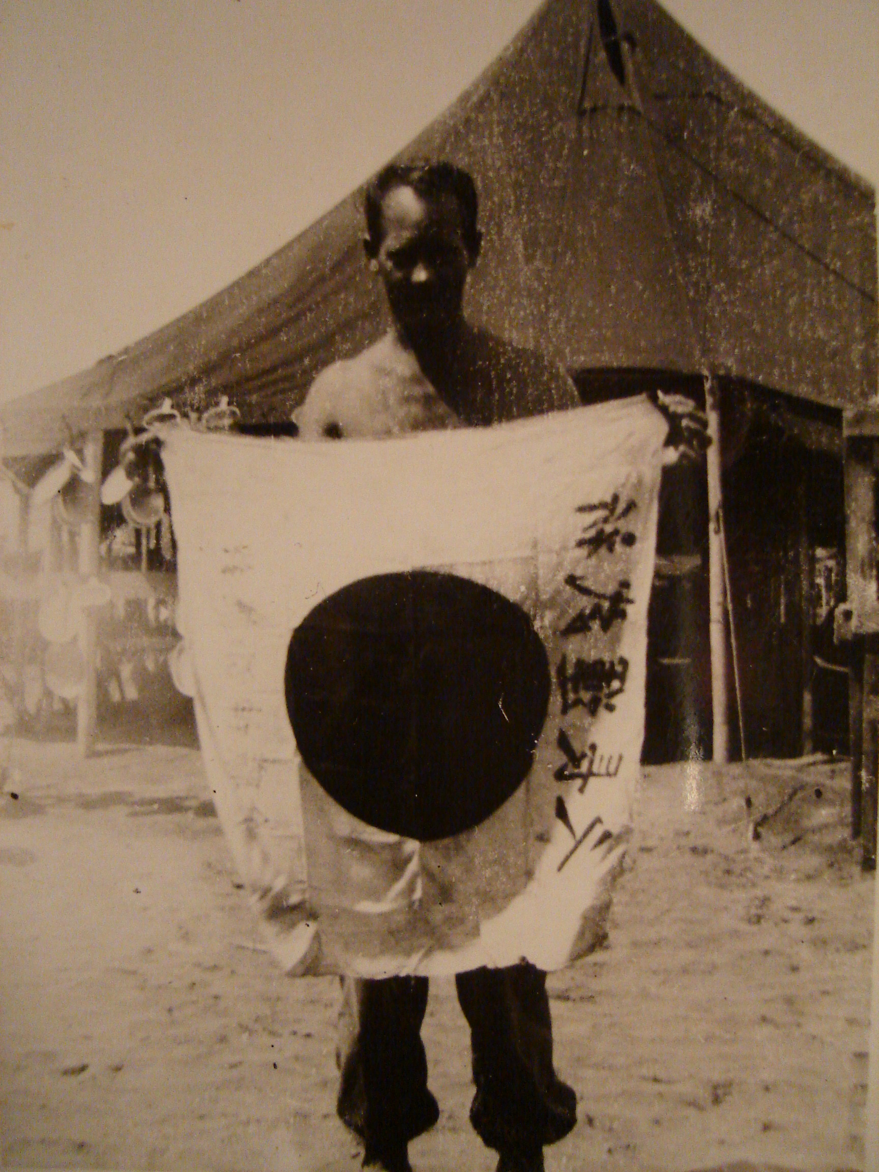 Charles_A_Coffman_Co_G_with_Captured_Japanese_Flag_Courtesy_of_Grandson_Matt_Oravik
